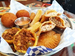 The Tapa Combo at Cafe Cubano features two papa rellenas, two empanadas, three ham and cheese croquetas, tostones rellenos and yuca frita.