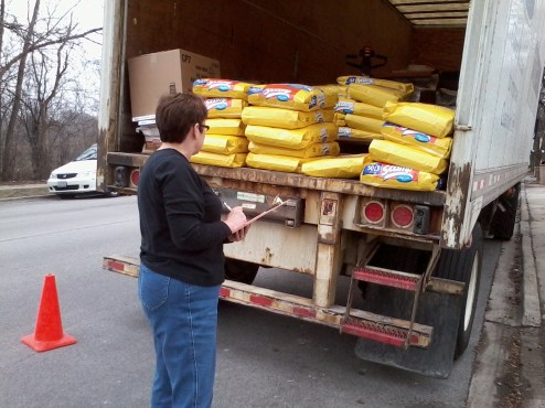 """Shelter Manager Marci Watt inspects a """"special delivery. """" Last year ACL used more than 20,000 pounds of cat litter."""