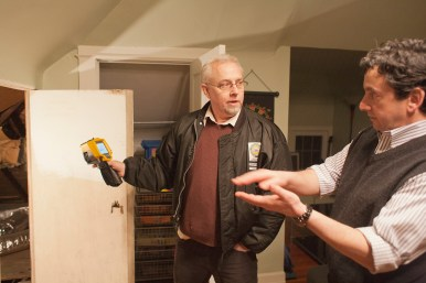 Eye-opener: Michael Ruehle, a BPI energy analyst, left, uses a thermal imaging camera to detect air leaks in the house of Monte Lewis during a recent energy assessment of his Oak Park home. Ruehle told Lewis he found areas where insulation could be improved and an energy savings of 15 to 30 percent could be realized.