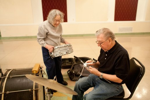 Neva Millonas, left, is the Mills Orchestra librarian, taking care of sheet music but also helping band members, including Albert Hasselman, set up for rehearsals and performances.