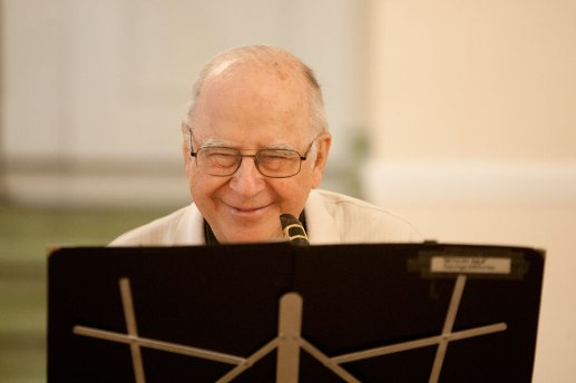 George Millonas laughs after he decides to scratch a number during rehearsal for the Mills Orchestra's final performance.