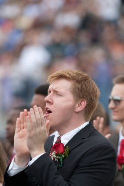A graduate gives a cheer after classmate John Clay III sang the Star Spangled Banner.