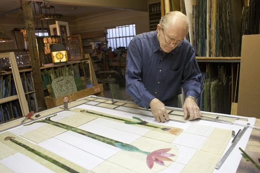 Glass Act: Bob Nugent joins pieces of stained glass with strips of lead on a lotus design window he is preparing for a home. Nugent's Tiffany Stained Glass Ltd. is on Desplaines Avenue in Forest Park. (DAVID PIERINI/Staff Photographer)