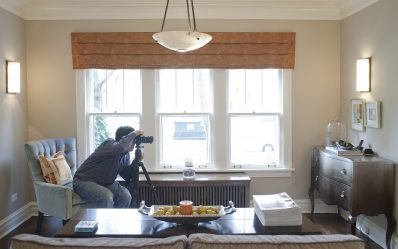 Lights, camera, still life: Goyette frames a corner of the living room and tries to solve issues with light falling on a very reflective piece of furniture. (Below) A lens becomes a decorative element during the shoot. (DAVID PIERINI/Staff Photographer)