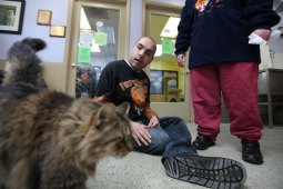 Here, kitty, kitty: Manny Rodriguez, 39, plays with a 10-year-old cat named Maserati last week.