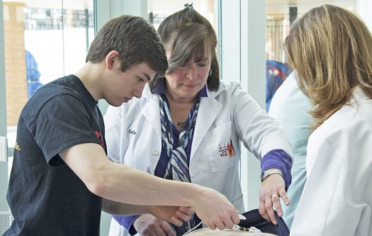 Volunteers from Young Hearts for Life prepare to run an electrocardiogram on a player from the OPRF Hockey Club (Courtesy Brian Cassidy)