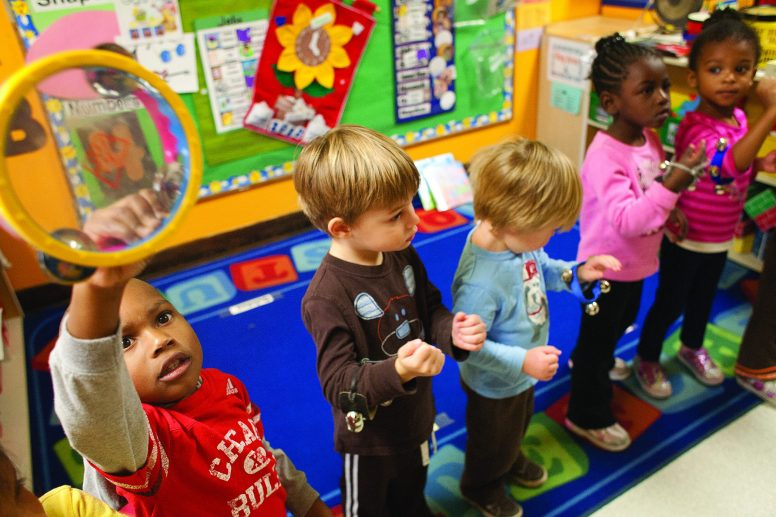 Quinton Nash, left, shakes a tambourine during a song in the Sunshine Room at the Oak Park-River Forest Day Nursery in 2012. | FILE