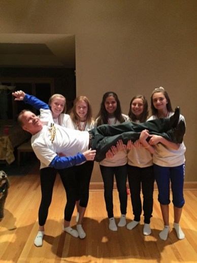 St. Luke eighth grade cross country runners, left to right, Aimee Morrissey, Jillian Johnson, Elena Vaccaro, Ava Vaccaro and Angelique Lorenzo give head coach John Morrissey a lift during the season. (Courtesy Anna Dooley)