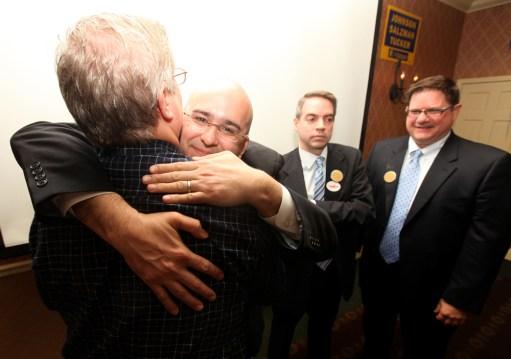Hugs all around: Adam Salzman hugs a supporter as Robert Tucker and Ray Johnson look on at the Carleton Hotel, Tuesday.Photos by J. GEIL/Staff Photographer