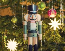 Toy soldier wooden nutcracker statue standing in front of decorated Christmas tree, vintage style