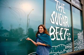 Gina Milkovich, education and outreach coordinator for Sugar Beet Food Co-op, 812 Madison St., shows the damage left by a single BB gun hole. It could cost thousands of dollars to repair. | ALEXA ROGALS/Staff Photographer