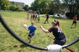 Henry Wright, 9, left, attempts to shoot the ball through the ring against Loyola University student Jessica Anger last Saturday, during a practice game of Quidditch at Scoville Park in Oak Park. (Alexa Rogals/Staff Photographer)