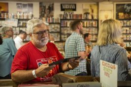 An attendee looks at a John Prine CD he bought last Thursday, June 6, during a private event at Val's Halla Records in the Arts District in Oak Park. | ALEXA ROGALS/Staff Photographer