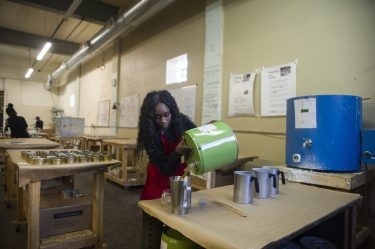 Team lead Natarah Grisby pours the candle scent into the mixture at Bright Endeavors in Garfield Park.   ALEX ROGALS/Staff Photographer