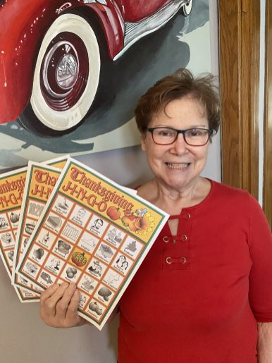"""Nora Abboreno holds up """"jingo"""" cards that were sent to family members so they could play a game together via Zoom on Thanksgiving."""
