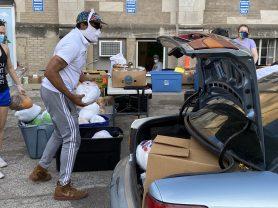 David Bradley, Beyond Hunger's distribution supervisor, loads a turkey into a car during drive through distribution.