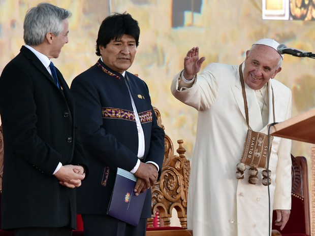 O Papa Francisco acena ao lado do presidente da Bolívia, Evo Morales, e do vice-presidente, Álvaro Garcia Linera, no aeroporto de El Alto, na quarta (8) (Foto: AFP Photo/Cris Bouroncle)