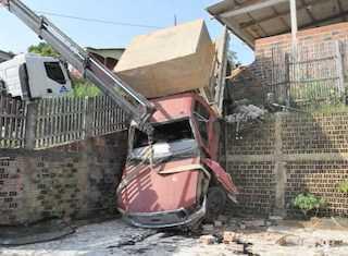 Parte da estrutura do caminhão ficou em cima de um muro de sustentação de um barranco/Foto: Juruá Online.