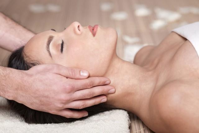 Happy woman receiving head massage over bamboo mat