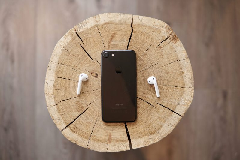 How to Start a Podcast - iPhone on a woodblock with AirPods