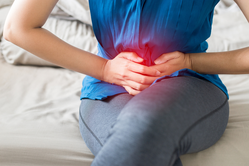 woman sitting on bed suffering from pelvic pain