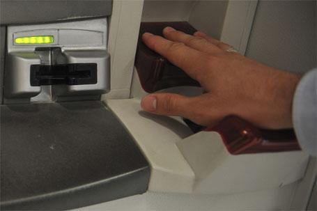 Imagem de um cliente usando o sistema biometria no caixa eletrônico