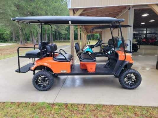Parked Orange 6 Person Premium Golf Cart