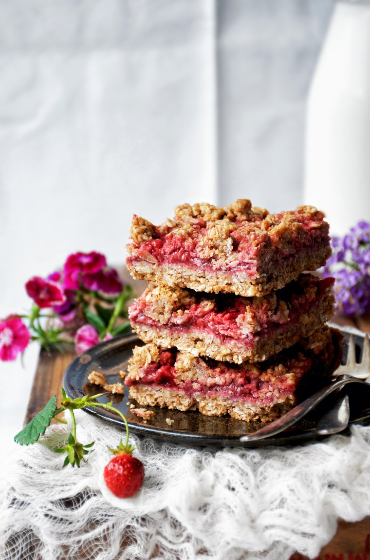 Three strawberry jam bars stacked on plate.