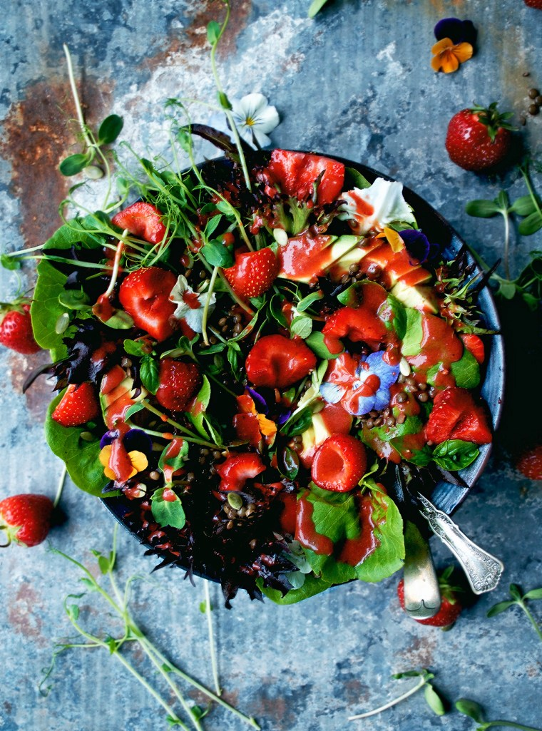 Strawberry and lettuce salad with sprouts, edible flowers, and a pink strawberry dressing in large bowl.