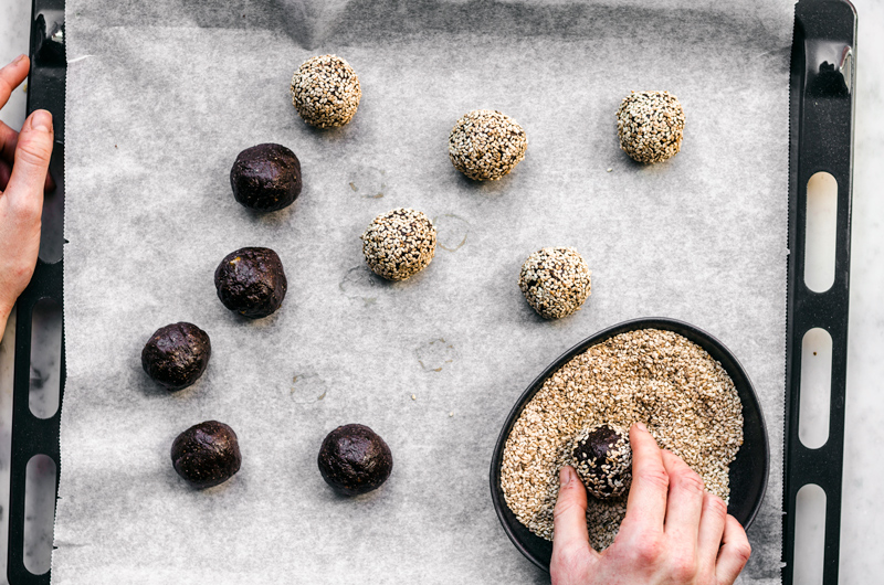 Chocolate cookie balls being rolled in sesame seeds.