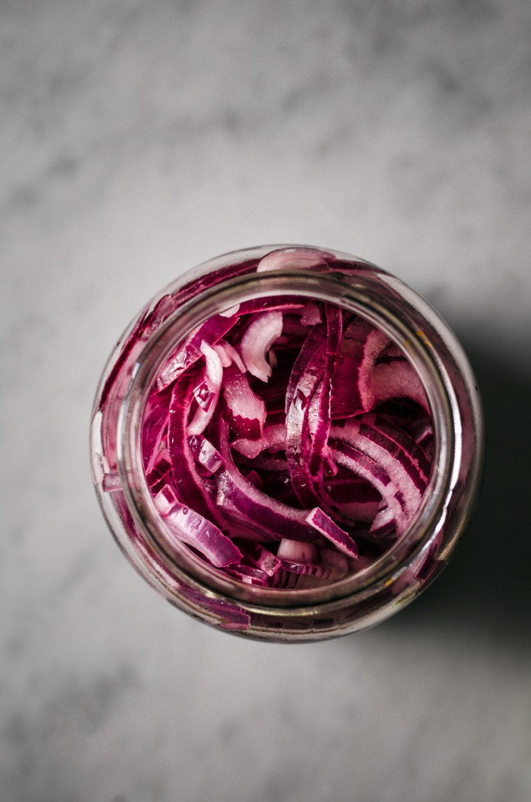 A jar of red onions for pickling, before they're fully pickled.