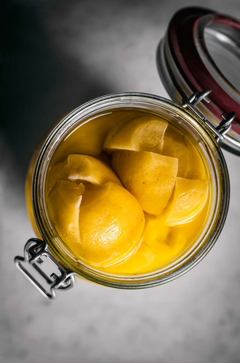 Preserved lemons in a flip top jar, lid open.