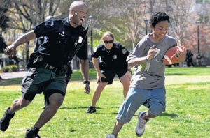 110319 Atlanta; Atlanta Police Department officer William Dorsey, left, chases Brandin McNair, 11, of Atlanta, during a football game with the APD officers against the kids at an APD Expo at Woodruff Park Saturday morning in Atlanta, Ga., March 19, 2011. Dorsey is part of the Atlanta Police Department Community Oriented Policing Unit. APD is hitting the street with a new community oriented policing unit that is to tie officers closer to neighborhoods instead of running from call to call. Jason Getz jgetz@ajc.com