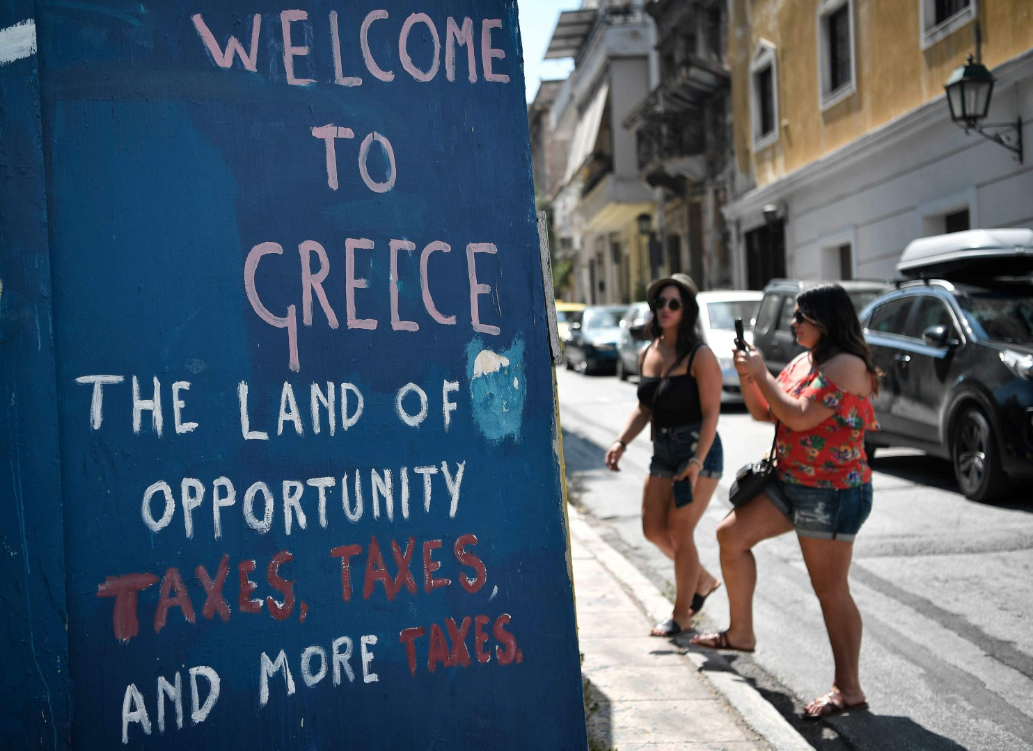 TOPSHOT - Tourists take pictures of slogans on a wall in central Athens, on August 18, 2018. - On August 20, Greece's third and final bailout officially ends after years of hugely unpopular and stinging austerity measures. The economy is growing slowly, and unemployment fell to below 20 percent in May for the first time since 2011. (Photo by LOUISA GOULIAMAKI / AFP)