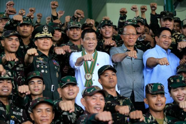 Philippines President Rodrigo Duterte clenches fist with members of the Philippine Army during his visit at the army headquarters in Taguig city, metro Manila