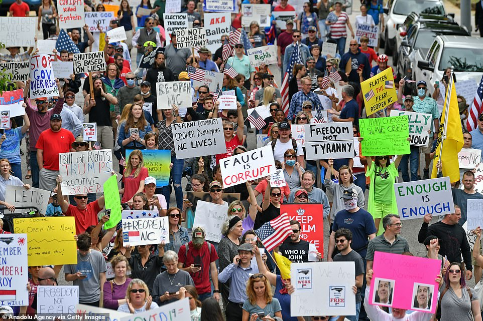 27480322-8242387-People_hold_up_signs_saying_Fauci_is_corrupt_Enough_is_enough_an-a-125_1587513930222