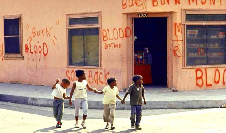 Children holding hands while crossing street, w. storefront in rear covered w. graffiti fr. '65 riots indicating black-ownership & support of violence.