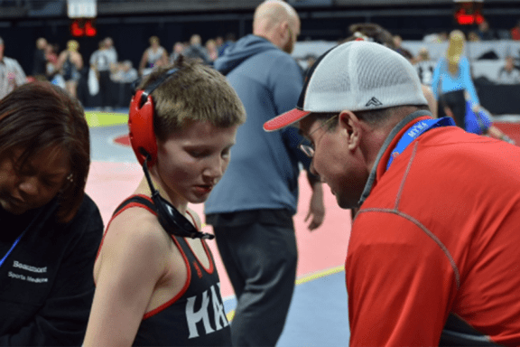 Robert Altland takes instruction from his father, assistant coach Brad Altland, after a match at the MHSAA state wrestling tournament
