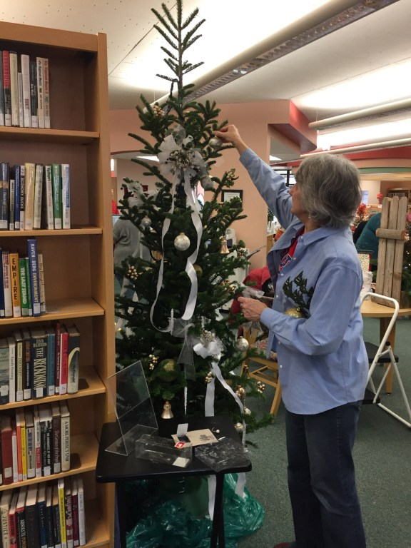 Janet Schultz decorates for the Celebration of the Trees at the Shelby Area District Library.