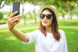 Smiling beautiful Asian woman in sunglasses taking selfie in summer park. Or pretty girl shooting streamed live for social media. Blogging concept