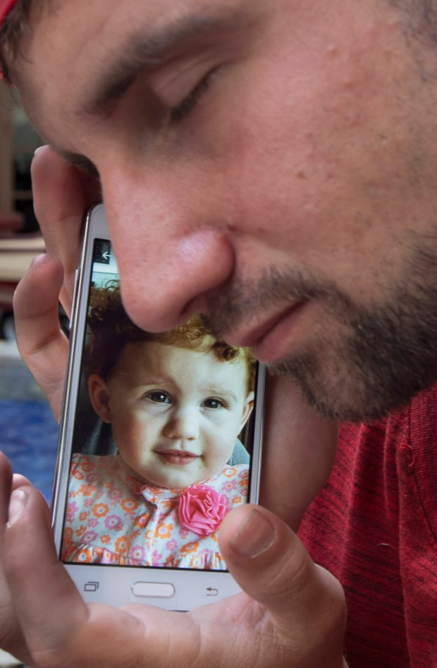 """Timmy cradles his cellphone showing a picture of his curly-haired toddler. He hasn't seen the 1 1/2-year-old girl in months because his ex-wife has a restraining order against him. The torture of losing his daughter is one of the things he talks about most when he gets stoned. """"All I've ever wanted to be was a father."""" (Photo by Mindy Schauer, Orange County Register/SCNG)"""