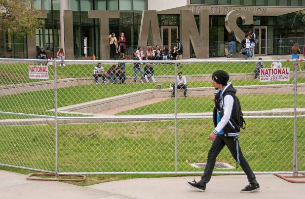 A student walks near a chain-link barrier on Monday, October 30, 2017, built around the Titan Student Union in anticipation of a demonstration against speaker Milo Yiannopoulos — a former Breitbart news site political commentator who will speak to students at the Fullerton campus Halloween night. (Photo by Ken Steinhardt, Orange County Register/SCNG)