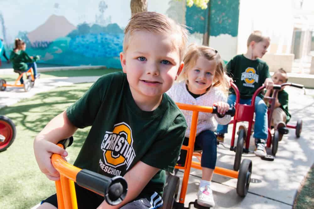 Ontario Christian Preschool students ride tricycles