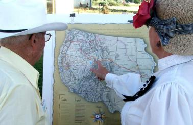 A man and a woman look at a map of western United States