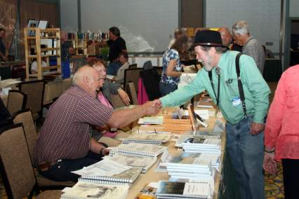 two men greet each other with handshake over a table covered with books