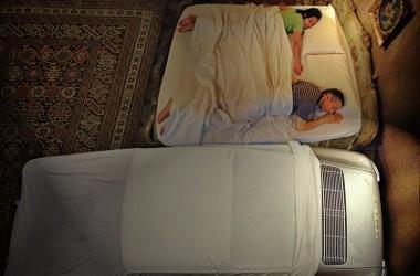 Ein Paar im Doppelbett und daneben liegt zugedeckt ein 911er