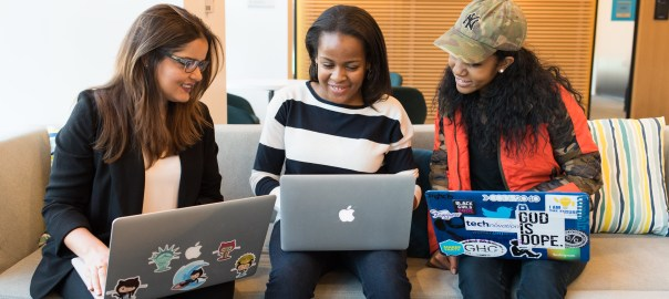 Three black women in tech sitting together with laptops