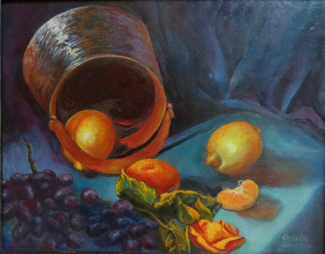 An oil painting of a brass pot surrounded by various fruit such as grapes and oranges.