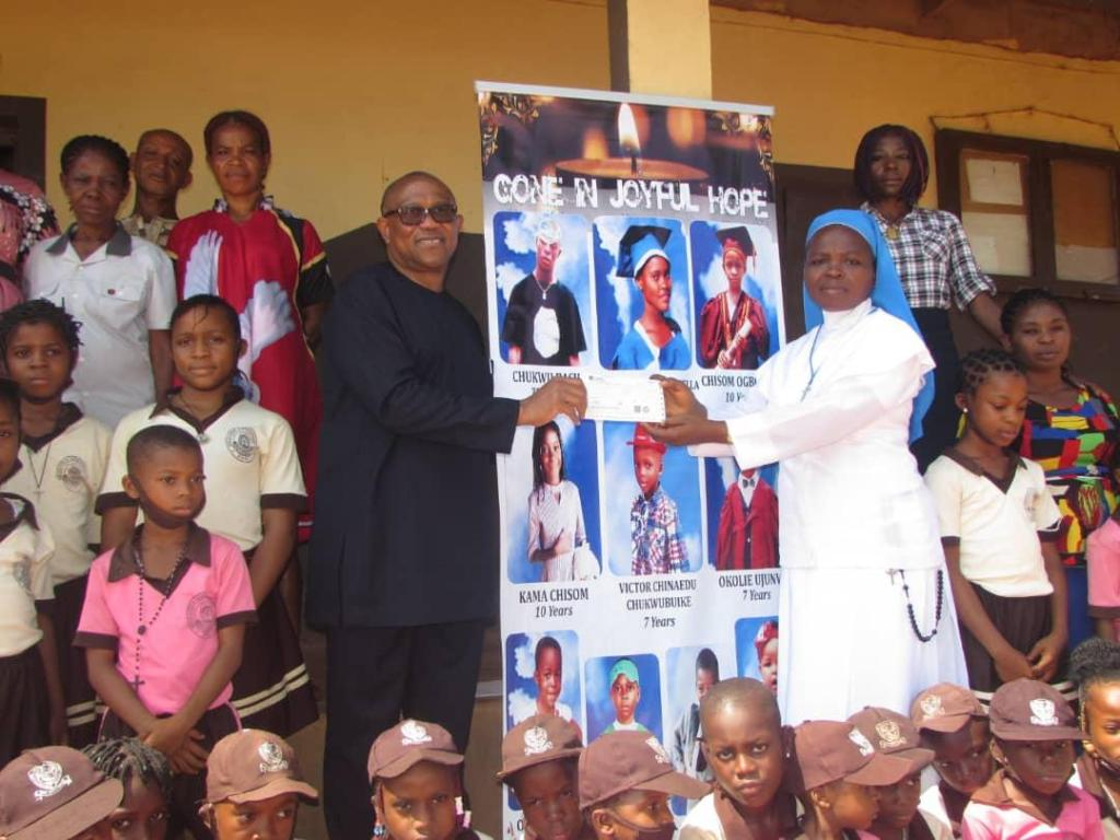 Rev. Sr Udechukwu Chidimma (right), receiving a cheque of N1 million Naira on behalf of Presentstion Nursery and Primary school, Awgbu, from Mr. Peter Obi (Left), who visited the school on Wednesday.