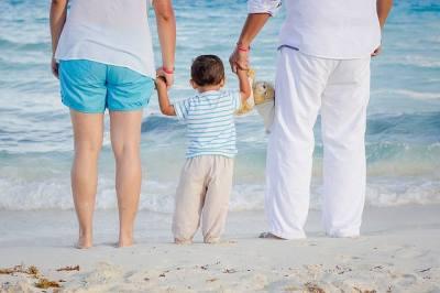 Dítě s rodiči na pláži